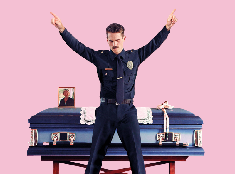 Jim Cummings' (star and director of Thunder Road) is dressed in a police uniform and is putting up a peace sign in front of a coffin.